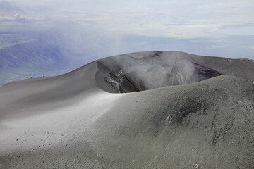 The crater of the new ash cone on Lengai volcano. Most of the time, a very fine, dilute stream of smoke (very fine ash, probably) is issuing from its crater. Note the 3 persons on the rim in the background: (Photo: Tom Pfeiffer)