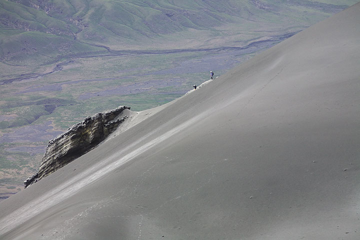 The group from before is trying to descend back along the old route, but will have to give up: the section beyond the rocks visible in the background is now a steep, smooth slope of hardened ash with no grip. (Photo: Tom Pfeiffer)