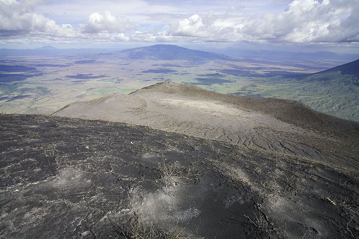 The south crater, now a desolate expanse of ash with all vegetation killed... Our tent is on its rim in the background, near where the new climbing/descending route starts, and as far as possible from the active crater... (Photo: Tom Pfeiffer)