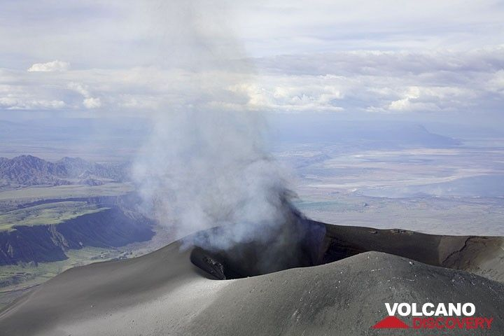 Shortly after the small group has crossed the crater floor, bluish gas exits the crater and a minute later, the first weak ash clouds.  (Photo: Tom Pfeiffer)