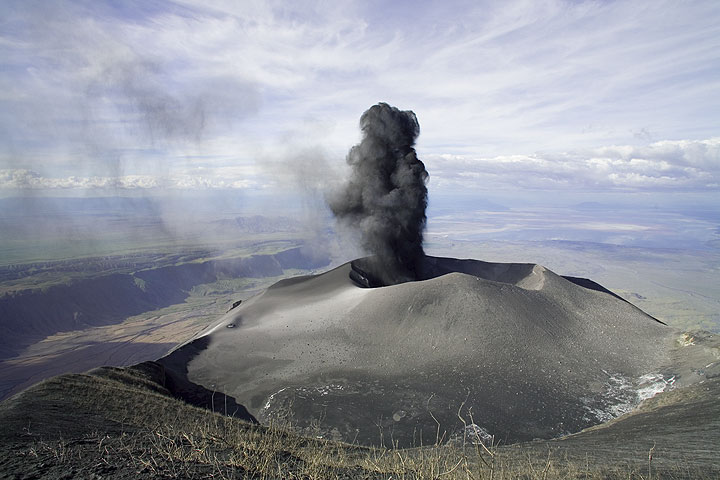 For comparison: a view from the same position in January 2008... Wide angle view of the northern crater with an eruption from the ash cone. Lake Natron and the Rift Valley can be seen in the background landscape 2000m below.  More from January 2008 at this page. (Photo: Tom Pfeiffer)