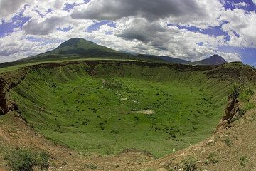 A large round crater lies along our way to Lengai. (Photo: Tom Pfeiffer)