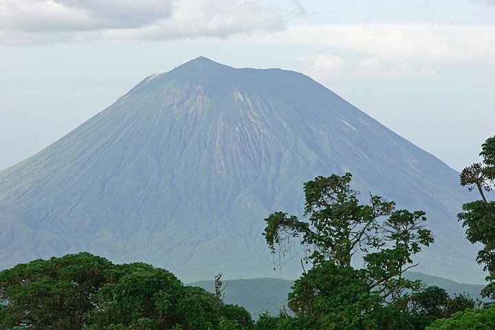 Ol Doinyo Lengai volcán visto desde el cráter Empakai. El hornito altura en su cráter activo (en el lado izquierdo) sólo picos fuera a la vista. (Photo: Tom Pfeiffer)