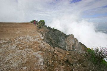 Two persons standing at the edge of the crater, which is filled to its rim; in some areas such as here, overflows have destabilized the rim and caused spectacular erosion by collapse of instable parts on the steep flank. (Photo: Tom Pfeiffer)