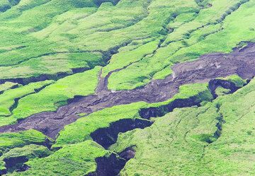 Erosion gullies at the feet of Lengai volcano and the still steaming lava flow from March 2006.  (Photo: Tom Pfeiffer)