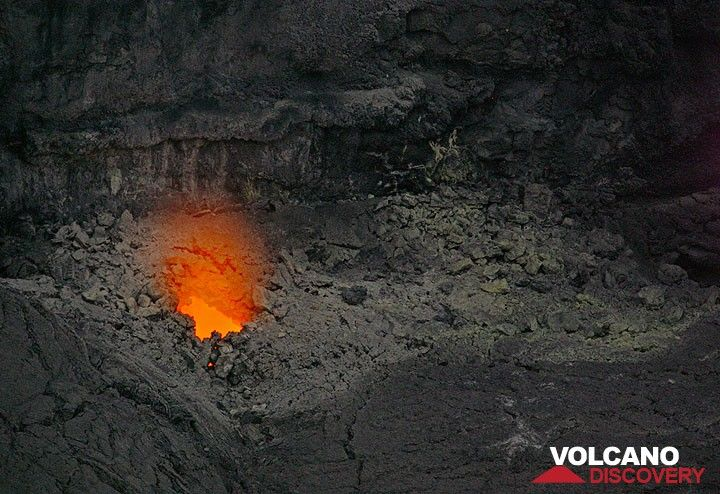 A weak glow from shallow magma is visible from one of the holes in the floor of the collapse pit. Moving magma is audible with sloshing sounds similar to a washing machine.  (Photo: Tom Pfeiffer)