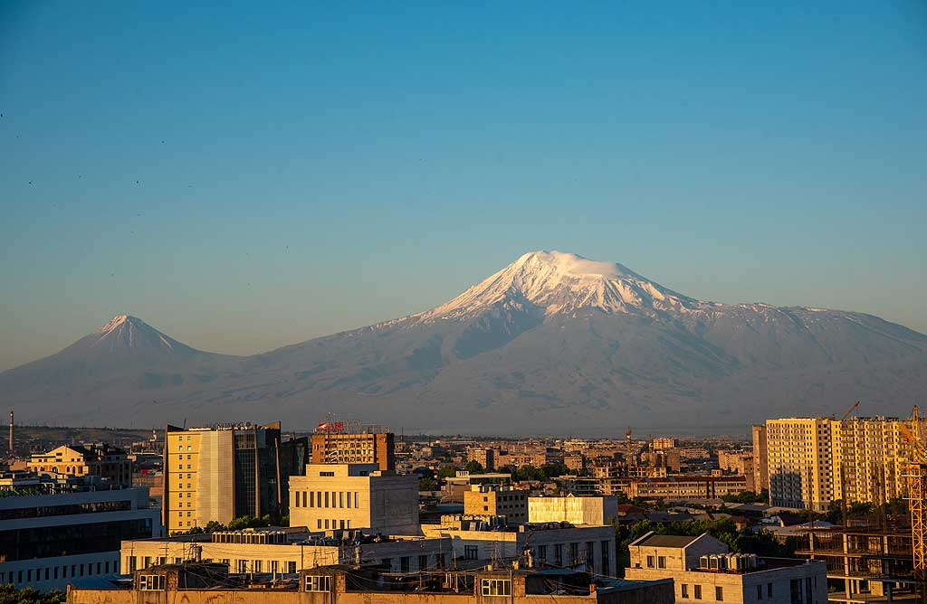 Sunrise has arrived in Yerevan and kisses the eastern facades of its buildings. On a clear morning, the slopes and valleys of Ararat volcano are well visible. (Photo: Tom Pfeiffer)