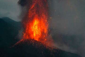 The lava fountains are nearly vertical, and a rain of incandescent bombs falls back around it. (Photo: Tom Pfeiffer)