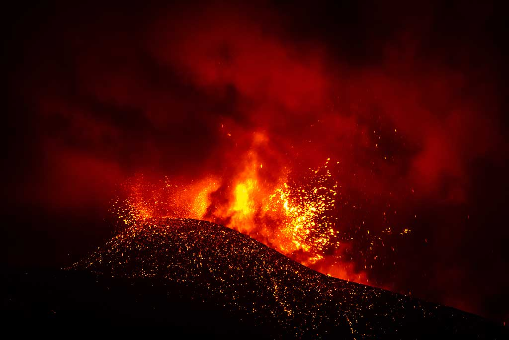 Later in the evening, the fountains becomes less steady, as the flow of magma seems to become interrupted by the rise of very large gas bubbles, that explode with loud detonations generating shock waves and throwing lava bombs in circular directions from the crater. (Photo: Tom Pfeiffer)