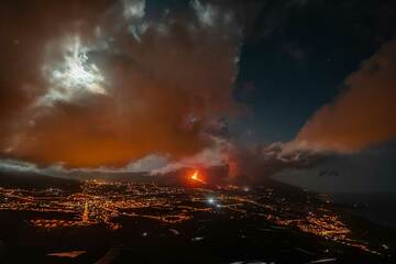 The eruption illuminating the broken clouds over the valley with red light from below. (Photo: Tom Pfeiffer)