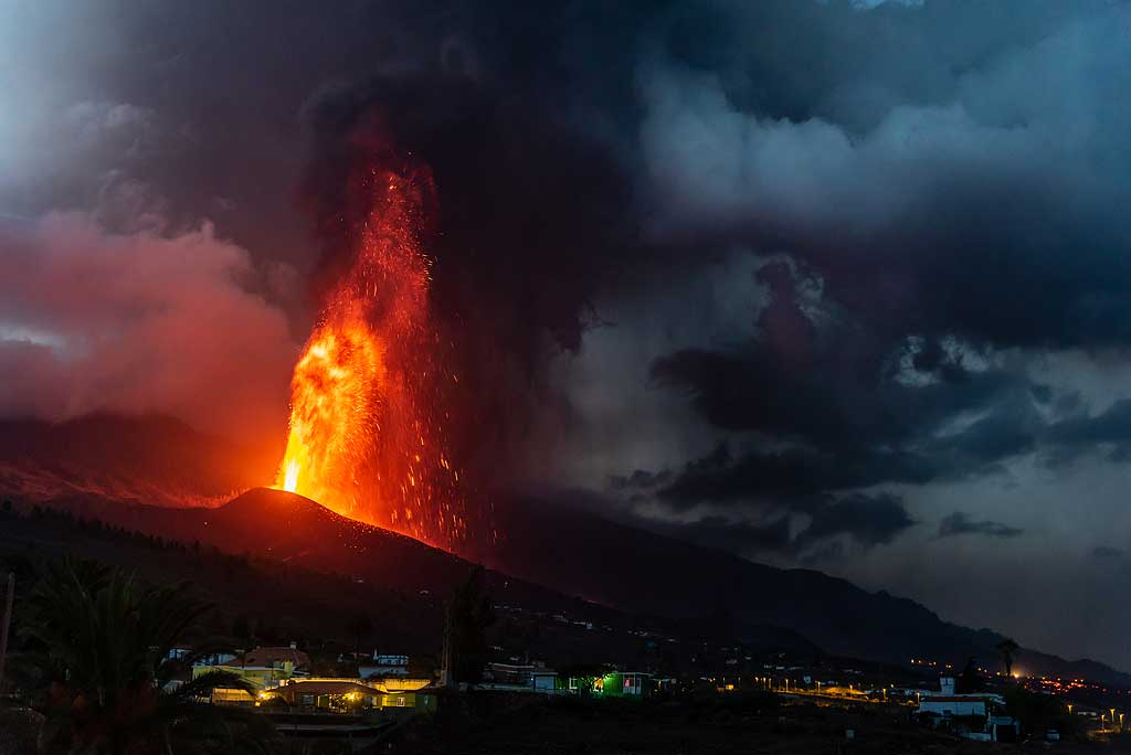 The activity remained fairly stable until noon of 24 Sep, characterized by sustained tall (4-500 m or more) lava fountaining, generating an eruption column and ash plume that rose 2-3 km, as well as constant lava effusion from the main vent. The latter formed a channeled surface flow that traveled about 1-2 km west from the vent, while a (probably more significant) part was likely directed into lava tubes feeding the flow field further below, which continued mostly to thicken and spread laterally. The following pictures mostly show the lava fountain and ash plume from various angles at distances from 3-8 km during the morning of 24 Sep. (Photo: Tom Pfeiffer)