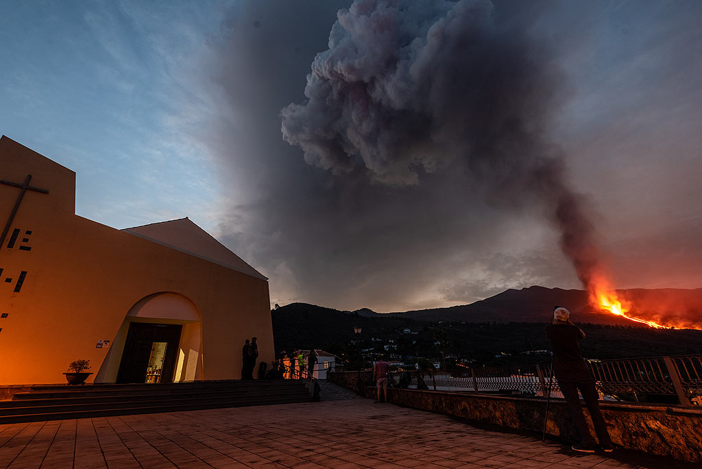 Dawn shows the large eruption column in more detail. Symbolically, one of the most visited places to watch the activity is the church. (Photo: Tom Pfeiffer)