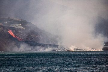 As it gets evening, when wind blows away the steam a bit, the active lava channel overtopping the coastal cliff and feeding the delta can be seen. (Photo: Tom Pfeiffer)