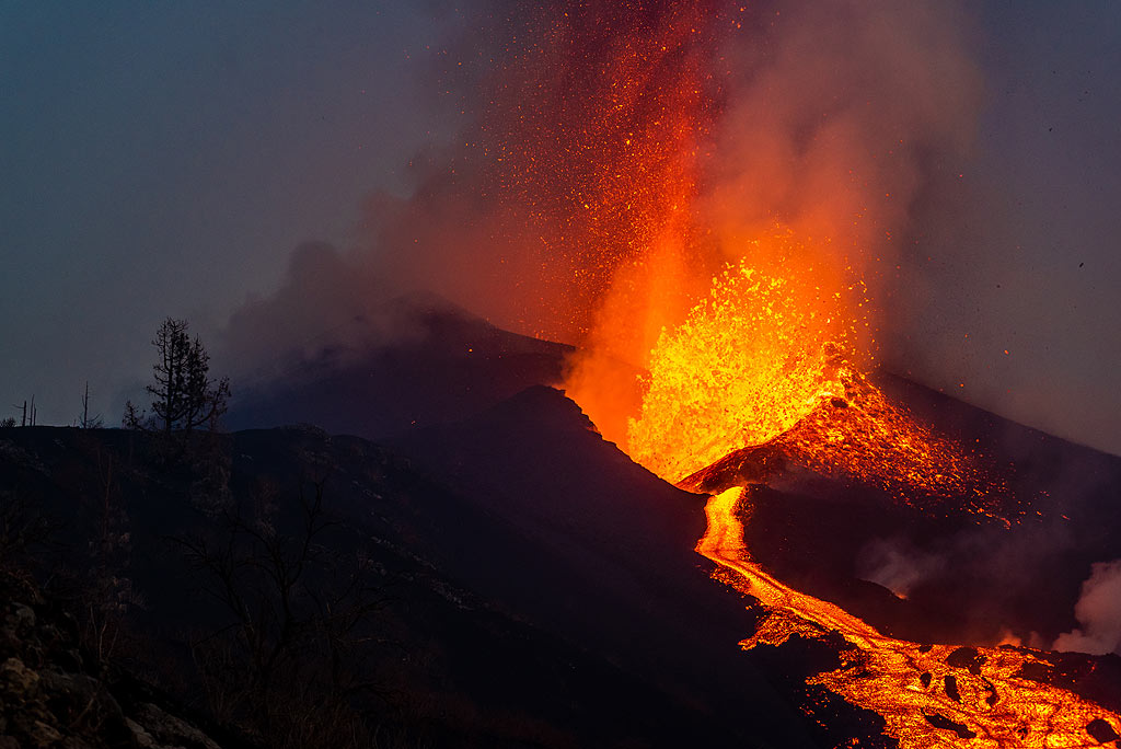 Lava fountain and lava flow at dusk with silhouettes of tree skeletons (Photo: Tom Pfeiffer)