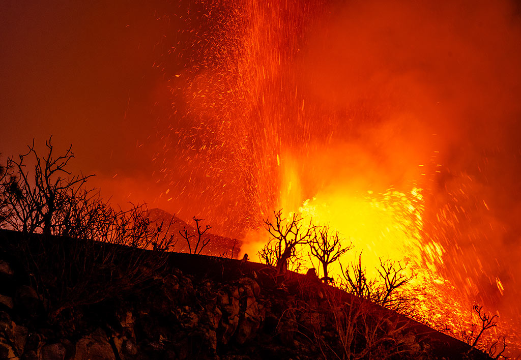 Silhouettes of vegetation with the eruption behind. (Photo: Tom Pfeiffer)