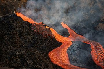 During 2 Oct, the activity continued without significant changes. At the cone, the flank vents remained active with lava spattering or low fountaining to feed lava flows, while pulsating lava fountaining became again stronger at the summit vents. The effusive vent north from the cone remained active with quiet lava effusion as well. Favorable wind conditions and a special permit from Guardia Civil provided us with unique observation opportunities from close range. (Photo: Tom Pfeiffer)