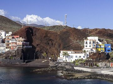 Houses and parts of the harbour of La Restinga built right into young cinder cones on the active SE rift zone of the volcano. (c)