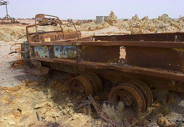 In den frühen Jahren des 20. Jahrhunderts bis in die 60er Jahre existierte am Dallol eine von Arbeitern bewohnte Stadt, die Pottasche abbauten. Die meisten Gebäude waren aus reinen Salzblöcken gebaut, die mit der Zeit zerfließen und auseinanderfallen. In der extrem aggressiven Umgebung des Dallol ist die Stadt und das Bergwerk, zu dem auch eine Eisenbahnlinie nach Eritrea gehörte, mittlerweile zu einem unscheinbaren Haufen von Ruinen und Rost verfallen.  (Photo: Tom Pfeiffer)
