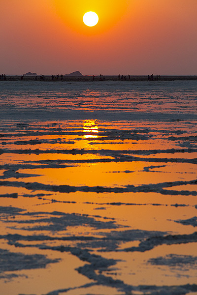The sun rises over the great salt lake in the northern Danakil desert, at 130 m below sea level, Africa's lowest point. The purple and orange sky is reflected in patches of water covering  hexagonal pieces of salt crust. The lake or salt plain consists of kilometer thick salt sediments that have accumulated over thousands of years in the lowest point of the Rift Valley. They are the result of intense evaporation when the area had been invaded by sea water from the Red Sea. The salt reaches about 4 km maximum thickness. In the background, silhouettes of workers are seen cutting salt blocks out of the crust of the lake. (Photo: Tom Pfeiffer)