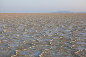 The endless expanse of the great salt plain Lake Assale located at 130 m below sea level in the northern Danakil depression near the Eritrean border. The surface crust forms hexagonal plates caused by evaporation and distribution of tension while the crust dries out. In this area, the salt deposit is several kilometers thick and tells about the tectonic force that rips Africa apart in this area, creating a deep trench, where sea water has invaded in the past and evaporated, leaving salt deposits behind. (Photo: Tom Pfeiffer)