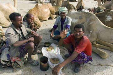 Während ringsum gearbeitet wird, ruhen sich die Kamelbesitzer und ihre Tiere noch aus. Erst wenn genügend Blöcke fertiggestellt sind, können die Kamele beladen werden. (Photo: Tom Pfeiffer)