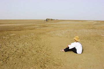 -120 m a.s.l. (I need to save on film, so we jump forward a bit). We are now in the northern part of the Danakil which is occupied by a mostly dry salt lake. Karinna watches the first salt caravans passing.  (Photo: Tom Pfeiffer)
