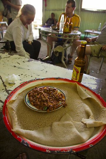 """In particular, if one opts for a typical local dish - """"tips"""" (spicy, diced grilled meat) with injera bread, which is eaten by hand to wrap the tips. This is best accompanied by a bottle of cool St. George beer!  (Photo: Tom Pfeiffer)"""
