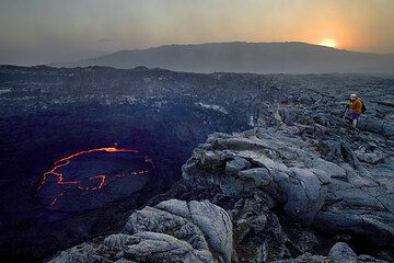 Franz taking photos of the lava lake while the sun is setting and creates a strange twilight. (Photo: Tom Pfeiffer)