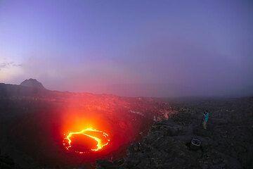 Erta Ale's lava lake at dusk and some of our party observing. (Photo: Tom Pfeiffer)