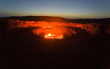 The lava lake after sunset; note the flashlights of observers on the rim above the lake. (Photo: Tom Pfeiffer)