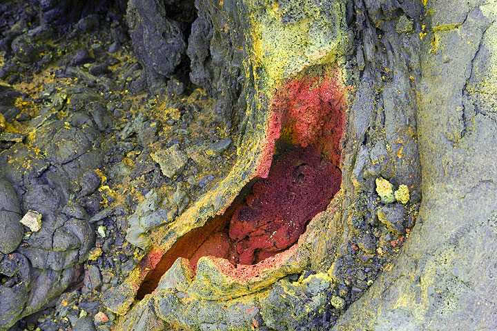 Red iron oxides and purple manganese oxides coat the interior of a small tube at the hornito. (Photo: Tom Pfeiffer)