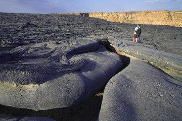 Beautifully shaped walls of a lava channel turning into a tube at the south of the crater. The caldera wall is in the background. (Photo: Tom Pfeiffer)