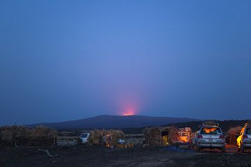 Base camp 10 km away from Erta Ale. The glow from the mountain's top is impressive and promising lots of activity. A short night's rest full of exciting apprehension lies in front of us... (Photo: Tom Pfeiffer)
