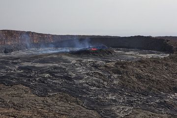 A first view of the south crater on 25 Nov 2010, from the western caldera wall. The crater is largely filled with overflows from the lava lake, and the lower northern rim of the crater has diappeared under overflows. (Photo: Tom Pfeiffer)