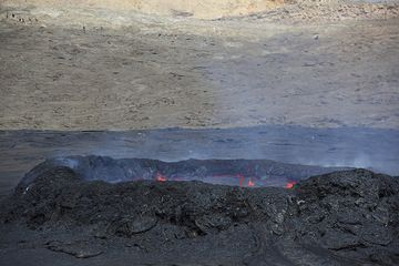 View of the lava lake standing relatively low inside the ring wall. Another group in the background on the caldera wall. (Photo: Tom Pfeiffer)