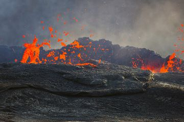 The lake has risen and the impressive lava fountains seen from the same height as the lava lake's surface. The heat blurs the air above the lake. (Photo: Tom Pfeiffer)