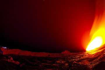 The illuminated crater wall of the south crater of Erta Ale volcano containing an active lava lake. At night, the lava shines bright red light over the landscape. A group of tourists stands on the rim to the left and watches the activity in the lava lake... (Photo: Tom Pfeiffer)