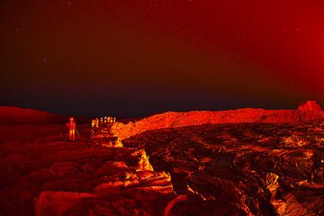 The illuminated crater wall of the south crater. A group of tourists stands on the rim and watches the activity in the lava lake... (Photo: Tom Pfeiffer)