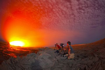 Two members from our group, Michel from Belgium and filmmaker Michael from Canada watching and photographing and filming the lava lake. The scene taken in extreme wide angle is illuminated by the strong glow from the lava and the light of the moon. (Photo: Tom Pfeiffer)