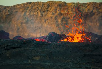 Lava fountains on the perched lake of Erta Ale in the morning. The caldera wall in the background. (Photo: Tom Pfeiffer)