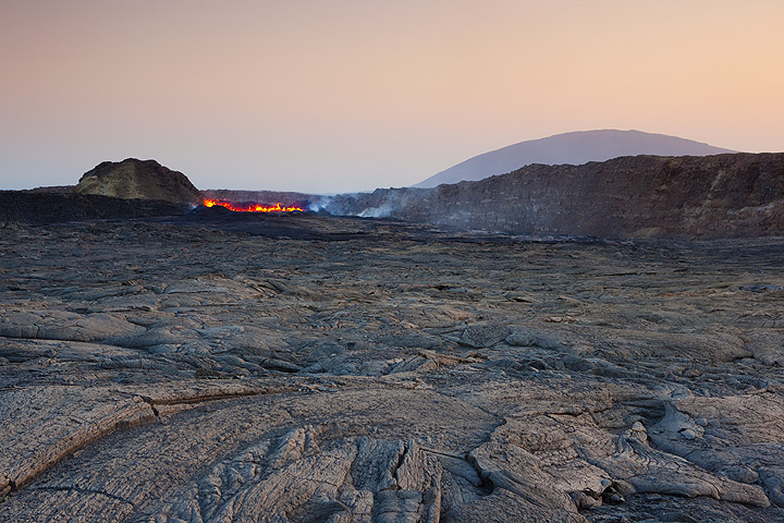 Wide angle view over the caldera with the lava lake in the center in front of a small cinder cone and the western caldera wall; in the distant background, another volcano looms over the scene. (Photo: Tom Pfeiffer)