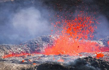 Magmatic gas escapes from the lava lake and creates spectacular fountains. The liquid lava is thrown many meters into the air, bursting into thousands of fragments. When liquid pieces are torn by the expanding escaping gas, lava is often torn into thin glassy threads, so-called Pele's hair. (Photo: Tom Pfeiffer)