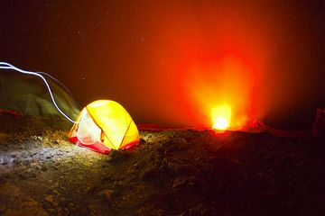 Tent perched on the crater of active Erta Ale volcano with its erupting lava lake in the center of the crater. The light of a person with a flashlight walking into the tent leaves a trace on the film. (Photo: Tom Pfeiffer)