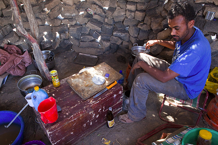 Asfau our cook in the improvized kitchen preparing lunch in one of the Afar huts before we return into the Danakil plain. (Photo: Tom Pfeiffer)
