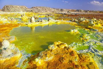Green pond with a yellow bubbling source at the lower left (Photo: Tom Pfeiffer)