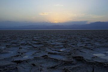 A mostly dried out part of the salt lake after the sun has sunken beneath the mountains on the horizon (Photo: Tom Pfeiffer)