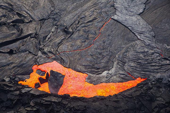 Die Kruste des Lavasees bricht am südlichen Seerand auseinander. Einzelne Platten tauchen ab und werden durch frisches heißes Magma ersetzt, das sofort neue Kruste bildet. (Photo: Tom Pfeiffer)