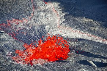 A spherical lava bubble bursts through the surface of the lake. (Photo: Tom Pfeiffer)