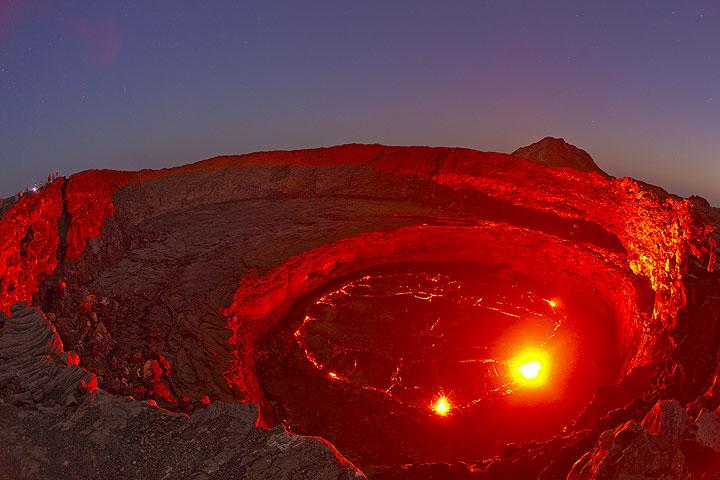 Der rote Schein der Lava beleuchtet die runden Kraterwände im abendlichen blauen Zwilicht. Beobachter am linken Kraterrand. (Photo: Tom Pfeiffer)