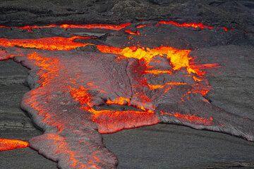 Ältere Kruste wird verschlungen. Die frische Lava, die aus den Zwischenräumen quillt, strömt auch über noch schwimmende alte Kruste hinweg. (Photo: Tom Pfeiffer)